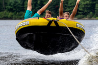 Three boys catch massive air while riding a tube behind a boat
