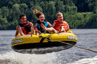 Three kids catching air in a tube being pulled behind a boat