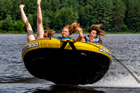 Three teen girls catching air on a tube being pulled behind a boat